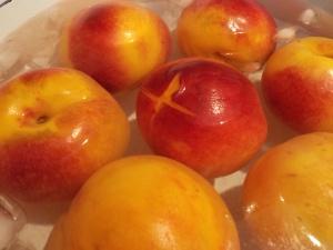 """Cut a small """"x"""" at the bottom of each peach"""